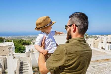 Father and little son walking on the island of Santorini