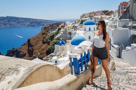 Young woman walks on the island of Santorini, Greece
