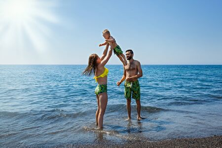 Father and mother swim and play with the child in the sea