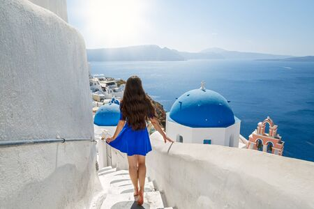 Young, beautiful woman walks up the stairs against the backdrop of the sea and the architecture of Greece