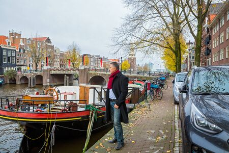 Man travels and walks along the Amsterdam waterfront