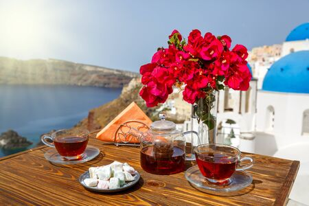 Tea and sweets on the table on the beach of Santorini