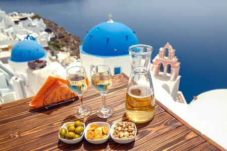 Bottle of wine and two glasses on the table, against the backdrop of the island of Santorini