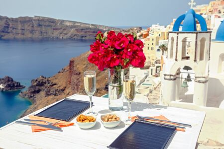 Two glasses of white wine on the table, against the backdrop of the island of Santorini Foto de archivo