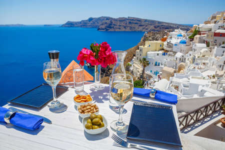 Wine and snacks on the table with a view of the Greek sea