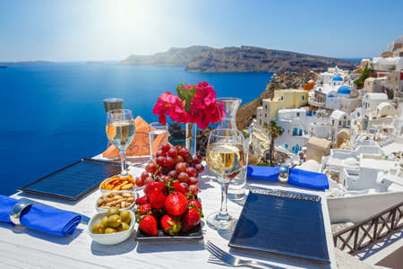 Wine, snacks and fruit on the table with a view of the Greek sea