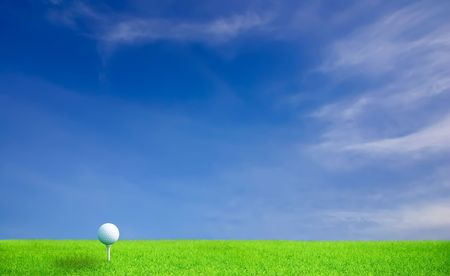 Golf ball on grass under blue sky and clouds