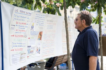 syndicate: NICE- JUNE 29: A man reading the banner of raising the retirement age from 60 to 62 on June 29, 2010 in NICE, FRANCE.