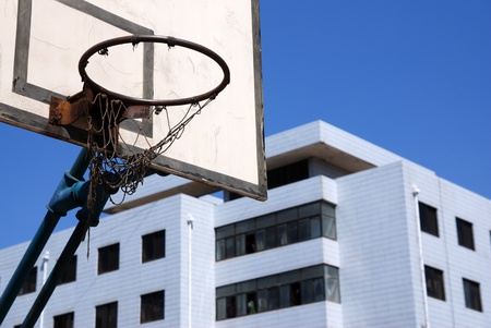 Outdoor basketball hoop against blue sky at an old school  photo