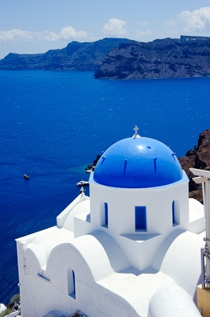 mediterranean houses: blue dome churches and classic cyclades architecture over the mediterranean sea in oia santorini island,greek  Stock Photo