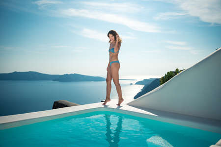 Beautiful girl lounging by the pool in Santorini island Greece