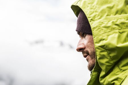 profile: Handsome man profile hooded man on the mountain is looking intently Stock Photo
