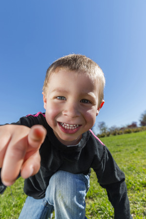 Child smiles at the park is pointing at camera Banco de Imagens - 39785883