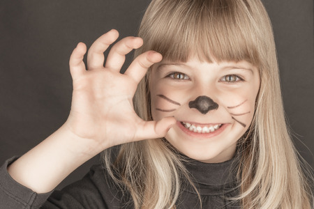 Sweet blond girl with cat costume smile and scratch