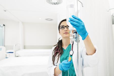 Jonge vrouw arts anesthesist gekleed in groene jurk, zet de pipet in het ziekenhuis kamer