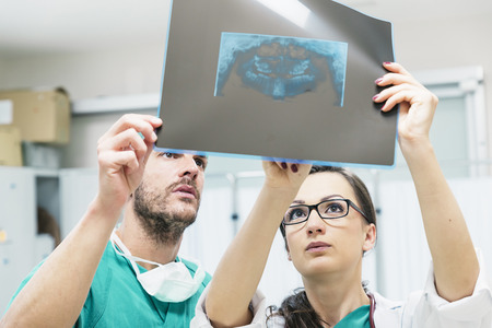 tomograph: Medicine dentist showing something to her male colleague on x-ray image. Healthcare and medical concept