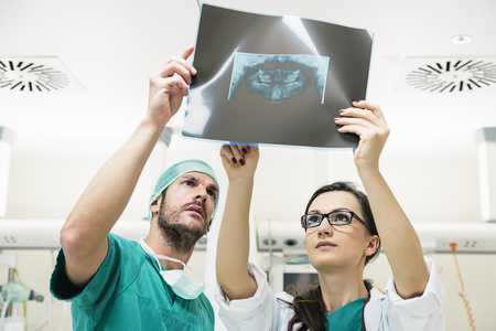 tomograph: Medicine doctor showing something to her male colleague on x-ray image. Healthcare and medical concept Stock Photo