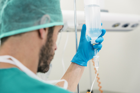 anesthesiologist: Young woman doctor anesthesiologist dressed in green gown, puts the dropper in hospital room