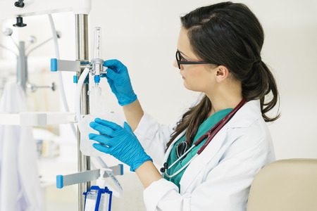 anesthesiologist: Young woman doctor anesthesiologist dressed in green gown, manipulating with flowmeter in hospital room