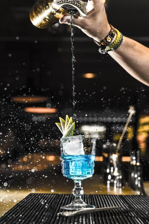 Barman pouring a cocktail into a glass at night club Standard-Bild
