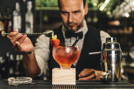 adding: Expert barman is making cocktail at night club