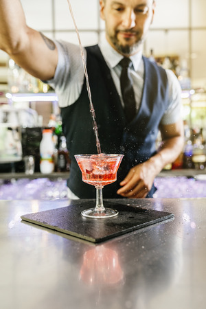 adding: Expert barman is making cocktail at night club.
