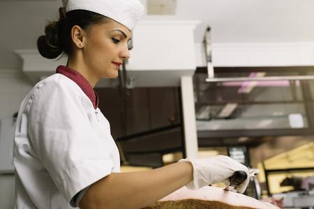 carniceria: Pretty butchery woman cutting ham with knife. Foto de archivo