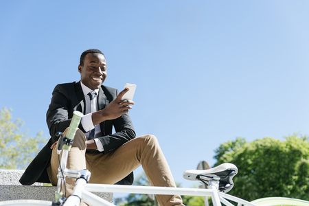 Portrait of Handsome african man smiling when he is using his mobile in the street. Standard-Bild