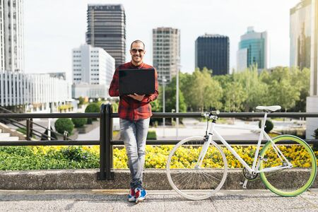 crewcut: Portrait of handsome young man with laptop  and fixed gear bicycle in the city.