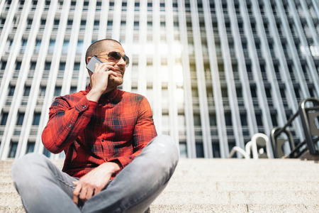 crewcut: Portrait of handsome young man with mobile phone in the city. Stock Photo