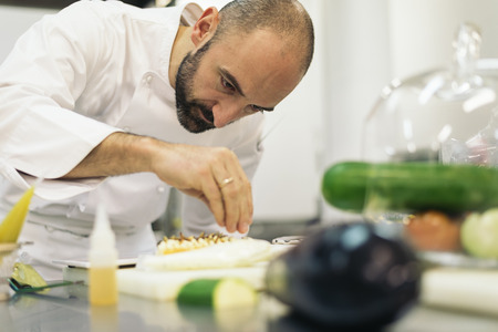 Hombre chef profesional cocinar en una cocina.