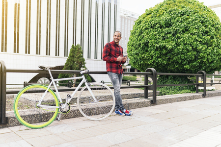 crewcut: Portrait of handsome young man with mobile phone and fixed gear bicycle in the city.