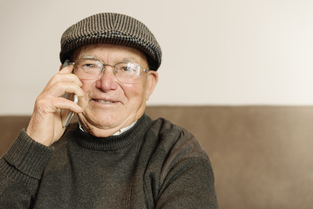Senior man using his mobile phone at home.