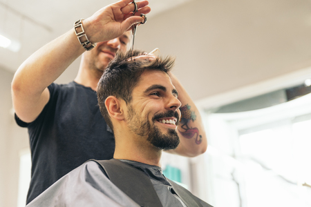 Hairstylist making men's haircut to an attractive man in the beauty salon. Stockfoto