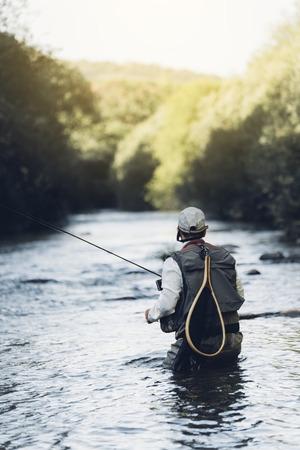はえの漁師は、美しい川でフライフィッシングの棒を使います。 写真素材