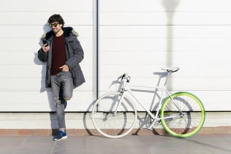Outdoor portrait of handsome young man with mobile phone and fixed gear bicycle in the street Stock Photo