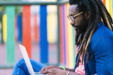 ノート パソコンで外に座っているアフリカ人の人の肖像画。都市の仕事の概念