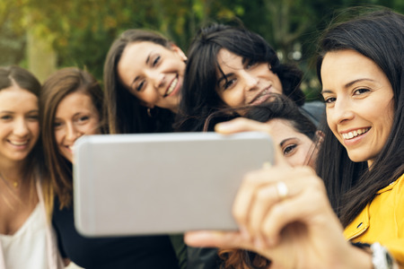 Portrait of six friends fun girls taking photos with a smartphone.