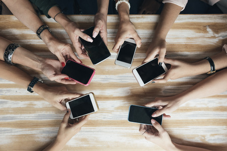 Top view hands circle using phone in cafe.