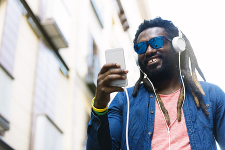 Outdoor Portrait Of Handsome African Young Man Listening Music.