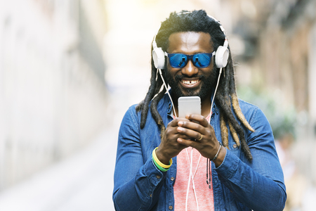 rastas: Retrato al aire libre del mensaje africano hermoso de la escritura del hombre joven y de la música que escucha.
