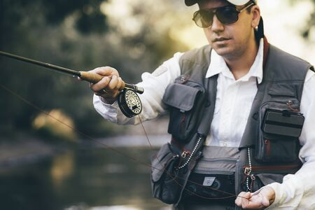 Fly fisherman using flyfishing rod in beautiful river.
