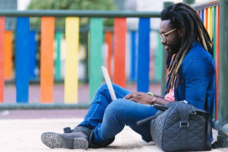 Portrait of african man sitting outside with laptop. Urban work Concept Stock Photo