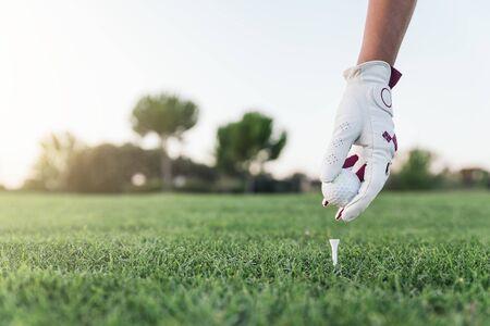 woman golf: Hand woman putting a golf ball on the tee. Golf Concept.