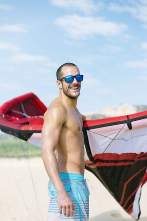 Portrait of handsome man kitesurfer in the beach.