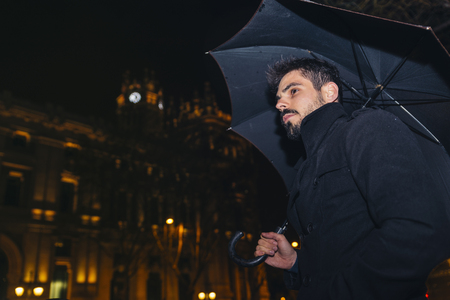 Handsome man walking in Madrid at night in the rain.