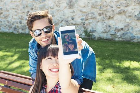Joven pareja feliz con smartphone sentado en el parque Foto de archivo