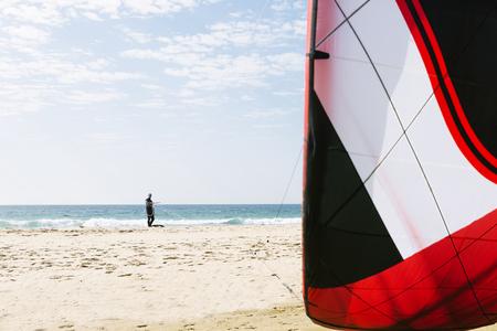 kiteboarding: Portrait of handsome man kitesurfer in the beach.