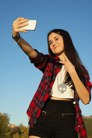 Portrait of Caucasian teener girl. Take a photo in the park