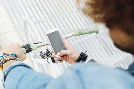 잘 생긴 젊은 남자가 휴대 전화 및 고정 된 자전거 거리에서 자전거.